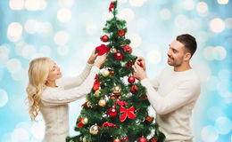 Happy couple decorating christmas tree over lights Stock Photography