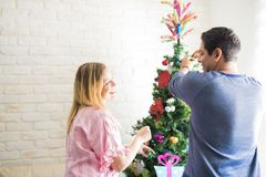 Happy couple decorating a Christmas tree. Rear view of a young couple having fun hanging some Christmas decorations together on a tree at home Royalty Free Stock Images