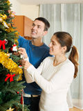 Happy couple decorating Christmas tree Stock Images