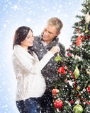 A happy couple decorating the Christmas tree Royalty Free Stock Photo