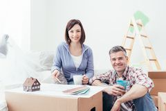 Couple designing their deam house. Happy couple designing their new house, they are checking the house project together and doing home renovations Royalty Free Stock Images
