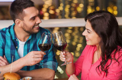 Happy couple dining and drink wine at restaurant. Leisure, celebration, food and drinks, people and holidays concept - smiling couple having dinner and drinking Royalty Free Stock Photography