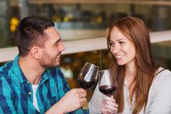 Happy couple dining and drink wine at restaurant. Leisure, celebration, food and drinks, people and holidays concept - smiling couple having dinner and drinking Royalty Free Stock Images