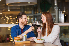 Happy couple dining and drink wine at restaurant. Leisure, celebration, food and drinks, people and holidays concept - smiling couple having dinner and drinking Stock Photos