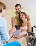 Happy couple with disabled wife talking with  social worker Stock Photo