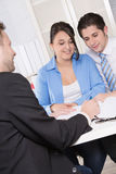 Happy couple discussing future financial plans with consultant a royalty free stock photo
