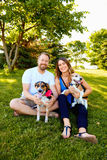 Happy couple of dog lovers sitting with their pets. Portrait of happy young couple of dog lovers sitting together on grass embracing their pets, looking at Royalty Free Stock Photography