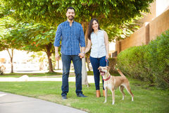 Happy couple with a dog. Portrait of a beautiful Hispanic couple going for a walk at a park with their friendly dog and smiling Royalty Free Stock Image