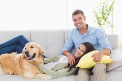 Happy couple with dog relaxing on sofa Stock Photos