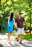 Happy couple with dog. Spend summer in city park Royalty Free Stock Images