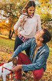 Happy couple with dogs playing outdoors in autumn park Stock Photo