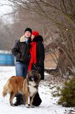 Happy couple with dogs in winter forest. Lovely moments outdoor royalty free stock photography