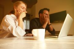 Happy couple doing business together working at small office on the laptop.  royalty free stock image