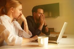 Happy couple doing business together working at small office on the laptop.  royalty free stock photography