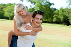 Happy couple doing piggybacking outdoors. Royalty Free Stock Photo
