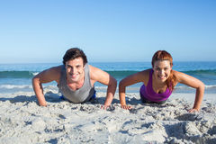Happy couple doing push ups together. At the beach Stock Photo