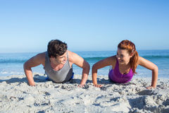 Happy couple doing push ups together. At the beach Stock Images