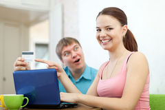 Happy couple doing shopping in internet. With credit card at home Stock Photo