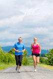 Happy couple doing sport jogging on rural street Stock Photography