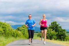Happy couple doing sport jogging on rural street stock photo