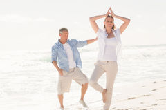 Happy couple doing yoga Stock Photos