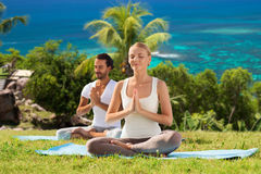 Happy couple doing yoga and meditating outdoors Royalty Free Stock Image