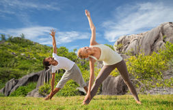 Happy couple doing yoga outdoors Stock Photos