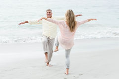 Happy couple doing yoga pose Royalty Free Stock Photos