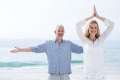 Happy couple doing yoga together Royalty Free Stock Images