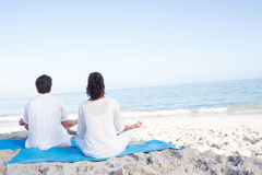 Happy couple doing yoga beside the water Stock Image