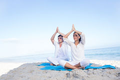 Happy couple doing yoga beside the water Royalty Free Stock Photo