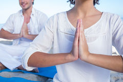 Happy couple doing yoga beside the water Stock Photography