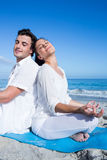 Happy couple doing yoga beside the water Stock Photo