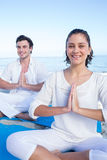 Happy couple doing yoga beside the water Royalty Free Stock Photos