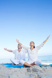 Happy couple doing yoga beside the water Stock Photos