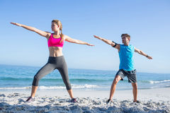 Happy couple doing yoga beside the water Royalty Free Stock Photography