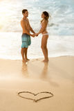 Happy couple with draw heart on sandy beach Stock Photography