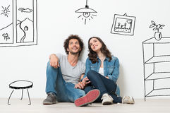 Happy Couple Dream New Home. Portrait Of Happy Young Couple Sitting On Floor Looking Up While Dreaming Their New Home And Furnishing royalty free stock images