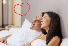 Happy couple dreaming in bed. Hotel, travel, relationships, and happiness concept - happy couple dreaming in bed Stock Image