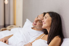 Happy couple dreaming in bed. Hotel, travel, relationships, and happiness concept - happy couple dreaming in bed Stock Photography