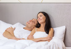 Happy couple dreaming in bed. Hotel, travel, relationships, and happiness concept - happy couple dreaming in bed Stock Images