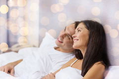 Happy couple dreaming in bed. Hotel, travel, relationships, and happiness concept - happy couple dreaming in bed over lights background Royalty Free Stock Photography