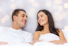 Happy couple dreaming in bed. Hotel, travel, relationships, and happiness concept - happy couple dreaming in bed over lights background Royalty Free Stock Photo