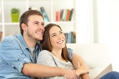 Happy couple dreaming looking above at home. Happy couple dreaming looking above sitting on a sofa in the living room at home Stock Photos