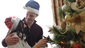 Happy couple dress up Christmas tree. At home stock video