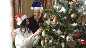 Happy couple dress up Christmas tree. At home stock video footage