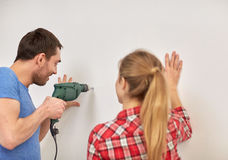Happy couple with drill perforating wall at home Stock Image