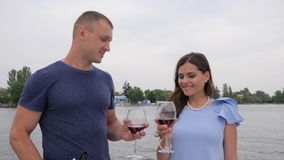 Happy couple drink red tipple in background sea, romantic twain people on vacation, glasses in hands man and female. Rest on water, male and woman drinking stock footage