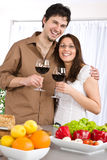 Happy couple drink red wine in modern kitchen Stock Photo