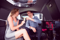 Happy couple drinking champagne in limousine Stock Photography